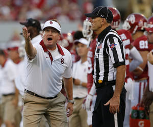 Photo - <p>OU coach Bob Stoops pleads his case to an official during Saturday's 41-3 victory against Akron in Norman. [Photo by Bryan Terry, The Oklahoman]</p>