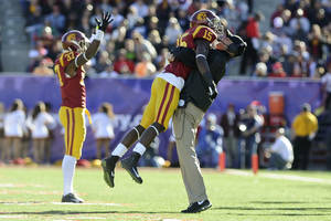 Photo - Southern California interim coach Clay Helton celebrates with wide receiver Nelson Agholor (15) after Agholor's 17-yard touchdown reception was ruled good against Fresno State in the second quarter of the Royal Purple Bowl NCAA college football game, Saturday, Dec. 21, 2013 in Las Vegas. (AP Photo/David Cleveland)