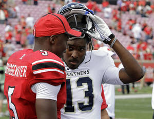 Photo - Louisville quarterback Teddy Bridgewater chats with Florida International quarterback E.J. Hilliard (13) after their NCAA college football game in Louisville, Ky., Saturday, Sept, 21, 2013. Bridgewater and Hilliard were high school teammates. (AP Photo/Garry Jones)
