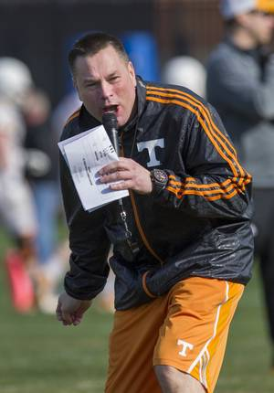 Photo - Tennessee head coach Butch Jones yells to his squad during spring practice Saturday, March 8, 2014, in Knoxville, Tenn. Jones has not set a timetable on when he will choose a starting quarterback. Jones said he'd decide on a starter whenever someone emerges as the clear-cut choice. (AP Photo/The Knoxville News Sentinel, Paul Efird)