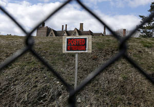 """Photo - FILE - In this Wednesday, March 27, 2013 file photo a """"no trespassing"""" sign and the roof of a mansion are visible from the path of the Cliff Walk, in Newport, R.I. Sixteen months after Superstorm Sandy washed away parts of Newport's famous Cliff Walk, a large swath remains closed. But officials say they expect the entire 3.5-mile trail will open again June 13 after millions of dollars is spent on repairs to the centuries-old walk, which attracts hundreds of thousands of visitors a year and is Rhode Island's most visited tourist attraction. (AP Photo/Steven Senne, File)"""