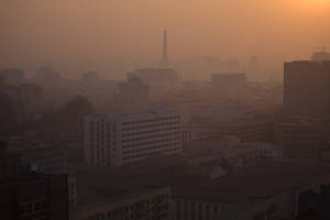 Photo - In this April 22, 2013 photo, the sun rises over Juche Tower in Pyongyang, North Korea. (AP Photo/David Guttenfelder)