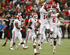 photo - Oklahoma's Aaron Colvin (14) celebrates after an interception with Demontre Hurst (6) during a college football game between the University of Oklahoma (OU) and Texas Tech University at Jones AT&T Stadium in Lubbock, Texas, Saturday, Oct. 6, 2012. Oklahoma won 41-20. Photo by Bryan Terry, The Oklahoman