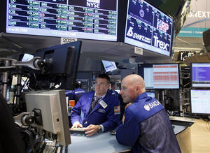 Photo - FILE- In this Friday, June 29, 2012, file photo Specialists Frank Masello, left, and John T. O'Hara work on the trading floor of the New York Stock Exchange in New York shortly before the closing bell. World stock markets rose Wednesday April 16, 2014 as China's slowdown in the first quarter was less severe than expected.    (AP Photo/David Karp, File)