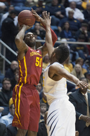 Photo - Iowa State's DeAndre Kane, left, looks to shoot over West Virginia's Terry Henderson during the first half of an NCAA college basketball game, Monday, Feb. 10, 2014, in Morgantown, W.Va. (AP Photo/Andrew Ferguson)