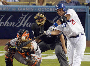 Photo -   Los Angeles Dodgers' Juan Rivera, right, hits a two-run home run as San Francisco Giants' Buster Posey catches and home plate umpire Larry Vanover watche during the eighth inning of a baseball game, Wednesday, Oct. 3, 2012, in Los Angeles. (AP Photo/Mark J. Terrill)