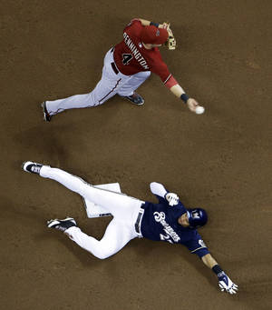 Photo - Milwaukee Brewers' Carlos Gomez is out at second as Arizona Diamondbacks shortstop Cliff Pennington turns a double play on a ball hit by Milwaukee Brewers' Scooter Gennett during the sixth inning of a baseball game Wednesday, May 7, 2014, in Milwaukee. (AP Photo/Morry Gash)