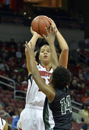 Photo - Louisville's Shini Schimmel, rear, gets a shot off over the defense of Wright State's Tay'ler Mingo during the first half of an NCAA college basketball game Saturday Dec. 7, 2013, in Louisville, Ky. (AP Photo/Timothy D. Easley)