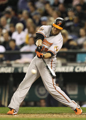 photo -   Baltimore Orioles' Chris Davis hits a two-run single against the Seattle Mariners to tie the game in the ninth inning of a baseball game, Tuesday, Sept. 18, 2012, in Seattle. (AP Photo/Ted S. Warren)