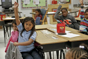 photo - Desks sit empty around Anna Tellez as she raises her hand to answer a question in Michelle Kenery's first grade class at North Highland Elementary on Tuesday, Jan. 15, 2013, in Oklahoma City, Okla. The school has been one of the most effected in the metro by the arrival of flu season.   Photo by Chris Landsberger, The Oklahoman