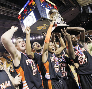 Photo - The Putnam City Pirates raise the gold ball championship trophy after their win over Midwest City in the 6A boys title game.  Photo by  Nate Billings,  The Oklahoman