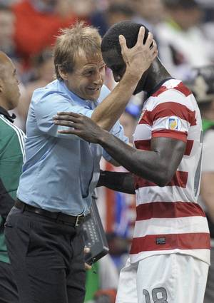 Photo -   U.S. manager Jurgen Klinsmann hugs forward Eddie Johnson as Johnson leaves the game late in the second half of a World Cup qualifying soccer match against Guatemala in Kansas City, Kan., Tuesday, Oct. 16, 2012. The United States won 3-1. (AP Photo/Reed Hoffmann)