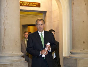Photo - House Speaker John Boehner of Ohio leaves his office and walks to the House floor to deliver remarks about negotiations with President Obama on the fiscal cliff, Tuesday, Dec. 11, 2012, on Capitol Hill in Washington. (AP Photo/J. Scott Applewhite)