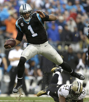 Photo - FILE - In this Dec. 22, 2013 file photo, Carolina Panthers' Cam Newton (1) hurdles New Orleans Saints' David Hawthorne (57) in the second half of an NFL football game in Charlotte, N.C. As Newton readies for his first playoff game, he says it's not about he and Colin Kaepernick but rather the Panthers against the 49ers on Sunda, Jan. 12, 2014.  (AP Photo/Bob Leverone, File)