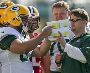 Photo - FILE - in this July 28, 2012, file photo, Green Bay Packers quarterbacks coach Ben McAdoo, right, center Jeff Saturday (63), quarterback Aaron Rodgers (12) and offensive guard T.J. Lang (70) talk during NFL football training camp in Green Bay, Wis. The New York Giants on Tuesday, Jan. 14, 2014, hired McAdoo as their new offensive coordinator. (AP Photo/Mike Roemer, File)