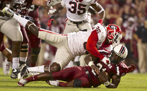 Photo -   South Carolina running back Marcus Lattimore is tackled by Georgia strong safety Shawn Williams during the first quarter of an NCAA college football game in Columbia, S.C., Saturday, Oct. 6, 2012. (AP Photo/Brett Flashnick)