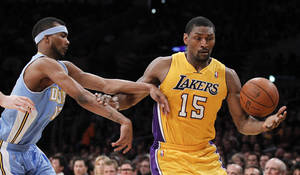 Photo - Los Angeles Lakers forward Metta World Peace, right, pulls in a loose ball away from Denver Nuggets forward Corey Brewer during the first half of an NBA basketball game in Los Angeles, Friday, April 13, 2012. (AP Photo/Chris Carlson) ORG XMIT: LAS105