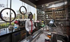 Photo -   In this photo taken Wednesday, Sept. 26, 2012, a member of staff prepares coffee at the cafe and wine bar of the Sankara Nairobi hotel in Nairobi, Kenya. International hotel developers are planning nearly 40,000 new rooms across Africa in the coming years, the continent's business travel is increasing, and Africa's middle class will soon begin leisure travel en masse. (AP Photo/Ben Curtis)