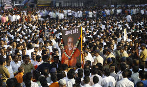 "Photo -   FILE - In this Nov. 18, 2012 file photo, Indian mourners carry a poster of Hindu hardline Shiv Sena party leader Bal Thackeray with the words ""Long Live"" during his funeral in Mumbai, India. Indian media say police in Mumbai have arrested two girls who posted a comment on a social networking site criticizing the shutdown of India's financial hub following the death of a Hindu fundamentalist politician over the weekend. (AP Photo/Rafiq Maqbool, File)"
