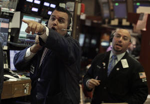 Photo -   Trader Bobby Finnerty, left, calls to a colleague on the floor of the New York Stock Exchange Wednesday, Aug. 1, 2012. Stocks are mostly higher in morning trading. (AP Photo/Richard Drew)