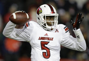 Photo - Louisville quarterback Teddy Bridgewater passes against Cincinnati in the first half of an NCAA college football game on Thursday, Dec. 5, 2013, in Cincinnati. (AP Photo/Al Behrman)
