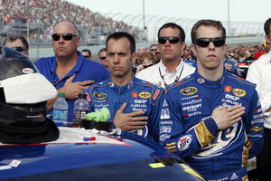 photo -   Brad Keselowski and members of his crew listen to the national anthem before the NASCAR Sprint Cup Series auto race at Homestead-Miami Speedway, Sunday, Nov. 18, 2012, in Homestead, Fla. (AP Photo/The Miami Herald, Andrew Uloza) MAGS OUT  