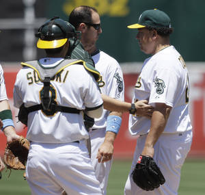 photo -   Oakland Athletics pitcher Bartolo Colon, right, is checked on by a trainer and catcher Kurt Suzuki (8) during the third inning of a baseball game against the San Diego Padres in Oakland, Calif., Sunday, June 17, 2012. Colon left the game after the play. (AP Photo/Jeff Chiu)