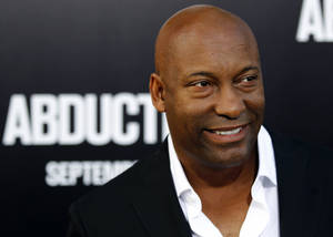 "Photo -   FILE - In this Sept. 15, 2011 file photo, director John Singleton arrives at the premiere of ""Abduction"" in Los Angeles. Court records show Singleton and Paramount Pictures on Nov. 1, 2012 settled a lawsuit filed by the director/producer that claimed the studio reneged on a contract to allow his company to produce two additional films after the release of 2005's ""Hustle & Flow,"" which received two Oscar nominations. (AP Photo/Matt Sayles, file)"