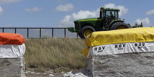 photo -   In this Sept. 6, 2012, photo, a tractor is used to farm in cotton field along a U.S.-Mexico border fence that passes through the property in Brownsville, Texas. Since 2008, hundreds of landowners on the border have sought fair prices for property that was condemned to make way for the fence, but many of them received initial offers that were far below market value. (AP Photo/Eric Gay)