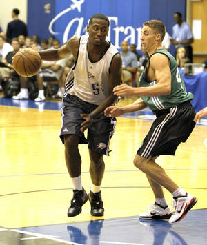 photo - Thunder guard Kyle Weaver makes a move around Boston's Jaycee Carroll during Monday's summer league game. AP PHOTO