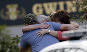 Photo - A group of people huddle together after an explosion and gunshots were heard near the scene where a man was holding four firefighters hostage Wednesday, April 10, 2013 in Suwanee, Ga. A police spokesman said the suspect was dead and none of the hostages suffered serious injuries.  (AP Photo/John Bazemore)