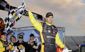Photo - Driver Matt Crafton celebrates in victory lane after winning a NASCAR Truck Series auto race at Martinsville Speedway in Martinsville, Va., Sunday, March 30, 2014. (AP Photo/Mike McCarn)