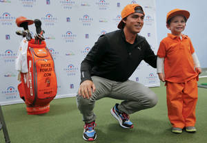 Photo - Former Oklahoma State golfer and current PGA pro Rickie Fowler poses for a photo with Micah Shadid, 3, while Fowler makes a special appearance at Golfsmith in Oklahoma City, Okla. as a surprise to members for the three Moore school's golf teams, Monday, Jan. 6, 2014.  .Photo by Chris Landsberger, The Oklahoman