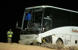 Photo -   An Arizona Highway Patrol officer examines the exterior of a tour bus that careened off the highway and crashed off northbound highway 93, Friday, Oct. 19, 2012, near Willow Beach, Ariz. The crash killed the driver and left at least four passengers with serious injuries. About 45 other passengers were less seriously hurt and not all of them required hospital treatment, the Arizona Highway Patrol said. (AP Photo/Julie Jacobson)