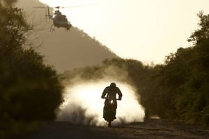 Photo - A TV helicopter follows Marc Coma, of Spain, as he rides his KTM motorcycle during the Dakar Rally between the cities of San Miguel de Tucuman and Salta, Argentina, Friday, Jan. 10, 2014. (AP Photo/Victor R. Caivano)