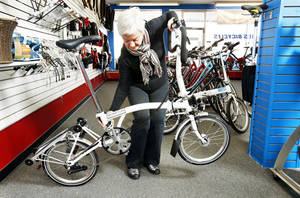 photo - Ann Ryan, co-owner of Als Bicycles, unfolds a Brompton bicycle as she explains how the folding bicycles work and why they are gaining popularity.
