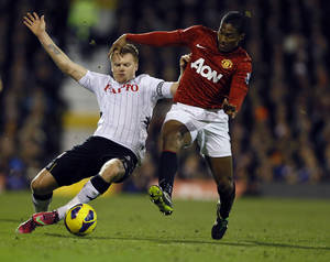 photo - Fulham's John Arne Riise, left, vies for the ball with Manchester United's Antonio Valencia during the English Premier League soccer match at Craven Cottage stadium in London, Saturday, Feb. 2, 2013. (AP Photo/Kirsty Wigglesworth)
