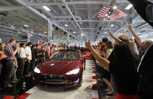 Photo - Tesla workers cheer one of the first Tesla Model S cars sold during a rally June 22 at the Tesla factory in Fremont, Calif.  AP Archives Photo