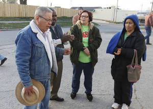 Photo - Volunteer Ramon Romero sings and prays with Spanish-speaking residents visiting the Jesus House for the annual Easter food basket distribution.  By Paul Hellstern, The Oklahoman <strong>PAUL HELLSTERN - Oklahoman</strong>
