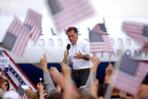 Photo -   Flags wave as Republican presidential candidate, former Massachusetts Gov. Mitt Romney speaks at Pueblo Weisbrod Aircraft Museum in Pueblo, Colo., Monday, Sept. 24, 2012. (AP Photo/Bryan Oller)