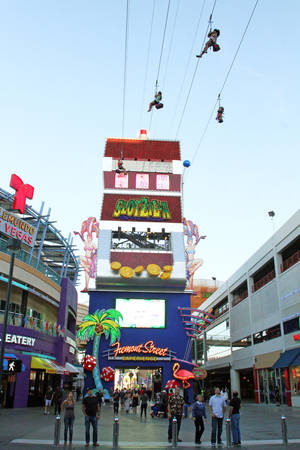 Photo - In this April 27, 2014 photo provided by the Fremont Street Experience, guests ride zip lines that swoop past the vintage casinos of downtown Las Vegas and under the giant video canopy of the Fremont Street Experience. The lower zip lines on the $12 million SlotZilla attraction opened over the weekend of April 26 after 14 months of construction. Rides start from a 12-story tower designed like a giant slot machine. Riders can now take the 77-foot-high zip lines, which harness visitors in a sitting position and take them 850 lateral feet to a platform near the 3rd Street Stage. (AP Photo/Fremont Street Experience, Scott Roeben)