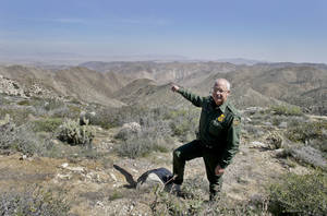 "Photo - In this Monday, March 25, 2013 photo, Border Patrol agent Richard Gordon, a 23-year veteran of the agency, points to a route used by illegal immigrants that runs through rugged mountainous terrain in the Boulevard area east of San Diego, in Boulevard, Calif. For the past 16 years, Gordon has been one of the top ""sign-cutters"" or trackers in the Border Patrol. (AP Photo/Lenny Ignelzi)"