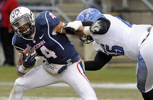 Photo - Connecticut wide receiver Deshon Foxx (4) is tackled by Memphis defensive lineman Latarius Brady (85) during the first half of an NCAA college football game in East Hartford, Conn., on Saturday, Dec. 7, 2013. (AP Photo/Fred Beckham)