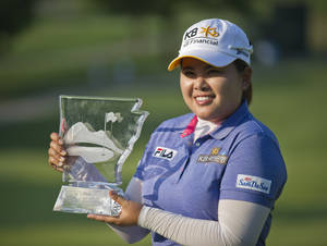 Photo - Inbee Park, of South Korea, holds the trophy on the 18th green following the final round of the LPGA NW Arkansas Championship golf tournament on Sunday, June 23, 2013, in Rogers, Ark. Park won the tournament in a playoff against compatriot So Yeon Ryu. (AP Photo/Beth Hall)