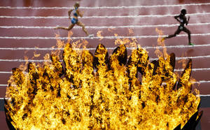 Photo -   Runners pass by the Olympics flame on the first day of the athletics in the Olympic Stadium at the 2012 Summer Olympics, London, Friday, Aug. 3, 2012. (AP Photo/Daniel Ochoa De Olza)
