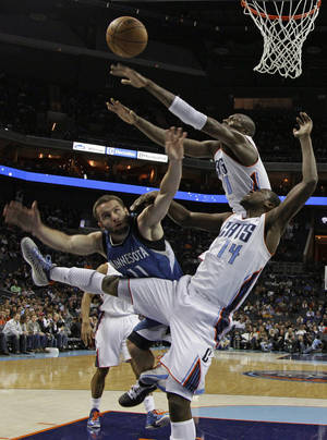 Photo - Minnesota Timberwolves' J.J. Barea (11) loses the ball as he drives between Charlotte Bobcats' Michael Kidd-Gilchrist (14) and Bismack Biyombo (0) during the first half of an NBA basketball game in Charlotte, N.C., Saturday, Jan. 26, 2013. (AP Photo/Chuck Burton)