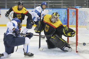 Photo - Karolina Rantamaki of Finland shots past Goalkeeper Jennifer Harss of Germany during the 2014 Winter Olympics women's ice hockey game at Shayba Arena, Sunday, Feb. 16, 2014, in Sochi, Russia. (AP Photo/Matt Slocum)