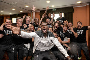 Photo - Juventus' Paul Pogba, foreground, celebrate with teammates after winning the Serie A overall soccer title, in a Turin hotel, Italy, Sunday, May 4, 2014. Juventus clinched its third straight and 30th overall Serie A title Sunday without even playing. With second-place Roma losing 4-1 at Catania, Juventus' eight-point lead became insurmountable because Roma only has two matches remaining. Juventus, which has three games to play, can celebrate when it hosts Atalanta on Monday although the Turin squad's players and coach Antonio Conte were already celebrating outside their team hotel wearing championship T-shirts. (AP Photo/Daniele Badolato, Lapresse)