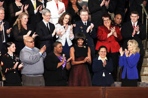 Photo - First lady Michelle Obama is applauded before President Barack Obama's State of the Union address during a joint session of Congress on Capitol Hill in Washington, Tuesday Feb. 12, 2013. Front row from left are Sgt. Sheena Adams, Nathaniel Pendelton, Cleopatra Cowley-Pendelton, Obama, Menchu Sanchez and Jill Biden. Second row from left are Oregon Gov. John Kitzhaber, Deb Carey, Tim Cook, Amanda McMillan, Lt. Brian Murphy, Marie Lopez Rogers, and Bradley Henning. (AP Photo/J. Scott Applewhite) ORG XMIT: CAP117