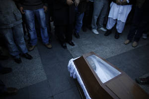 photo - Mourners  gather in front of the coffin carrying the body of Shehzad Luqman, a Pakistani immigrant who was murdered on Thursday after being stabbed by suspected extreme rightists, during a ceremony  in front of the city Hall in Athens on Saturday, Jan. 19 2013. An estimated 3,000 people marched  through central Athens in protest at a spate of anti-immigrant attacks that turned fatal Thursday when a 27-year-old Pakistani immigrant was stabbed by suspected extreme rightists.  (AP Photo/Kostas Tsironis)